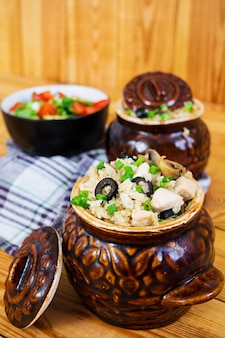 Rice with chicken, mushrooms and olives on wooden
