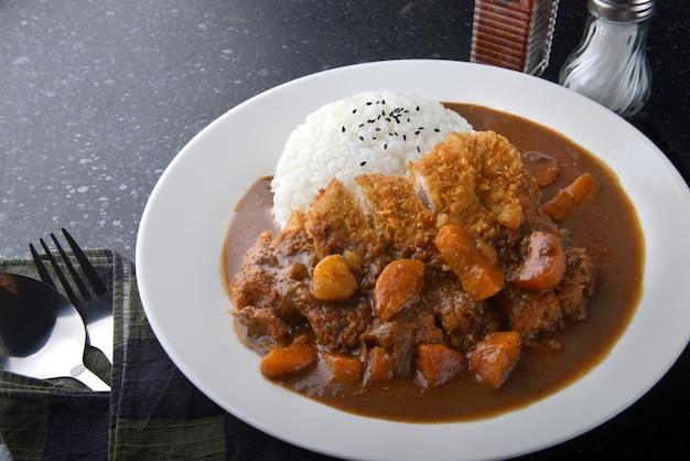 튀긴 돼지고기와 일본식 카레를 곁들인 밥이나 하얀 접시에 가쓰 카레.