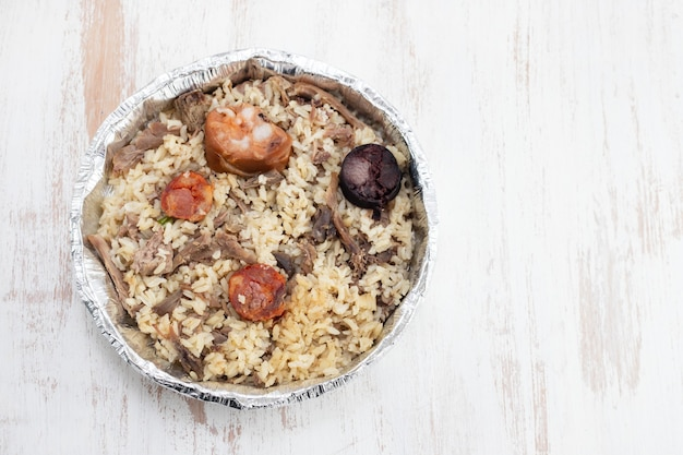 Rice with duck and smoked sausages in plastic box