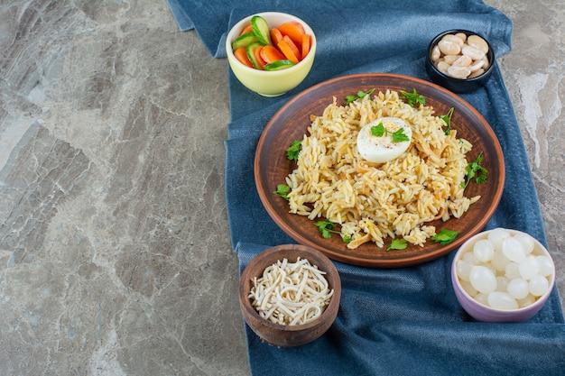 Рис с яйцом на тарелке рядом с различными материалами на кусках ткани, на мраморе.