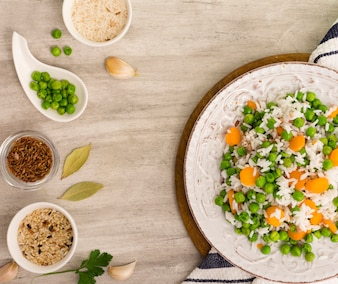 Rice with green beans and carrot on plate with bowls