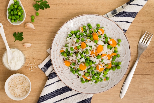 Rice with green beans and carrot on plate near sauce in bowl on table