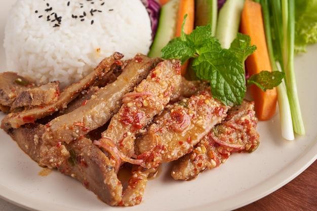 豚首のグリルご飯。ハーブとスパイスの材料を使ったポークサラダタイ料理のグリル、新鮮な野菜を使った伝統的な北東部料理、ホットでスパイシーなスライスグリルポークメニューのアジア料理。