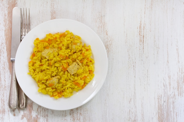 Rice with meat and carrot on white plate