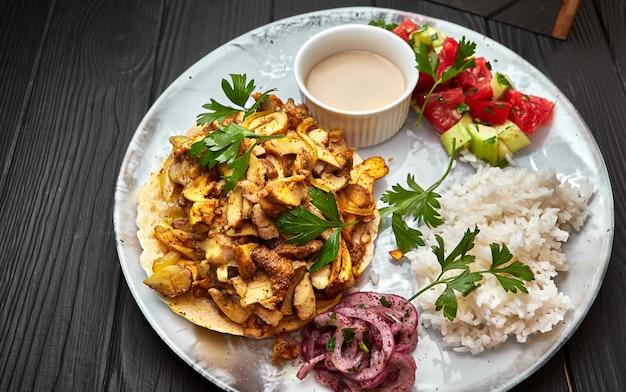 黒の背景に肉、キノコ、野菜、ピタ、ソースとご飯
