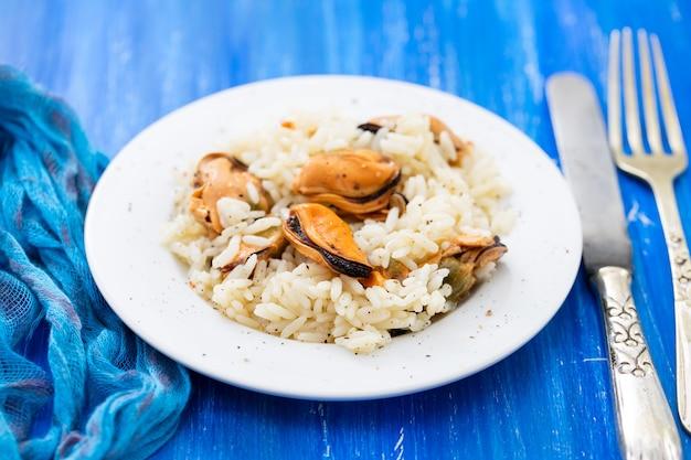 Рис с мидиями на маленькой белой тарелке на синем деревянном фоне