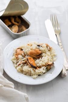 Рис с мидиями на маленькой белой тарелке на керамическом фоне