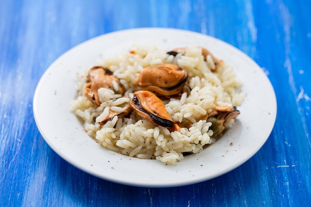 Rice with mussels on small white plate on blue wooden background