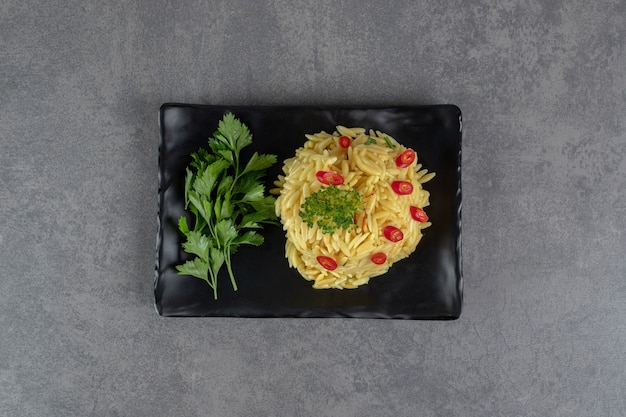Рис с дольками перца и зеленью на черной тарелке. фото высокого качества