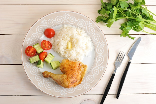 Rice with roasted chicken leg and cucumber with tomatoes on plate