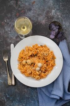 Рис с морепродуктами на белой тарелке и бокал белого вина