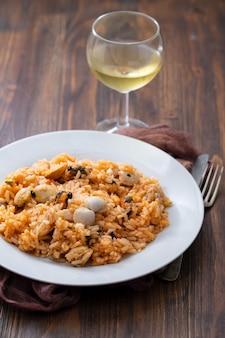 Рис с морепродуктами на белой тарелке на коричневом деревянном фоне