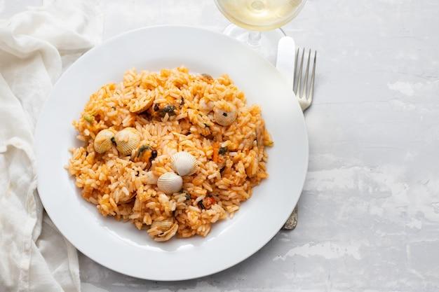 Рис с морепродуктами на белой тарелке на керамическом фоне