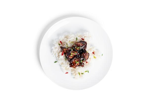 スパイシーチキンと唐辛子の甘酸っぱいソースでご飯。ゴマの照り焼きチキン。白い背景で隔離。高品質の写真