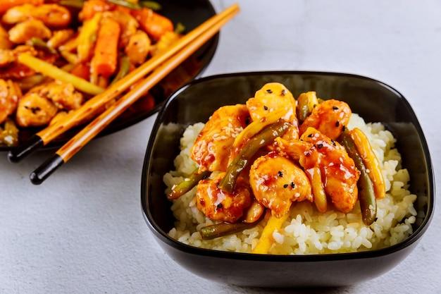 Рис с жареной курицей и овощами на черной квадратной тарелке. китайская кухня.