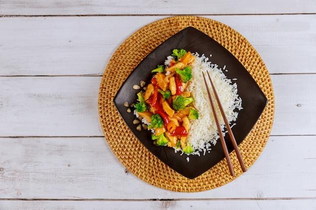 炒め物チキンと野菜の黒い正方形のプレート。中華料理。