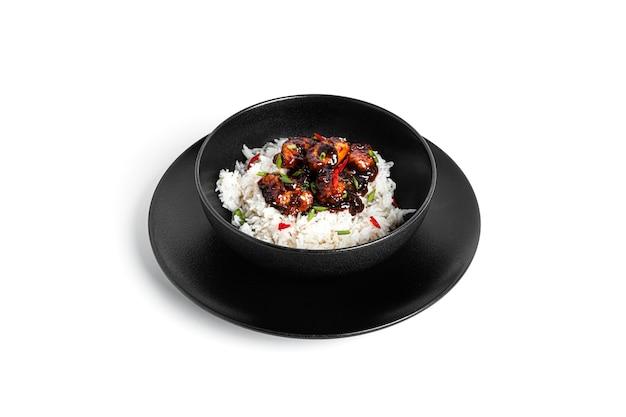 Рис с курицей терияки в черном изолированном блюде. японская кухня.