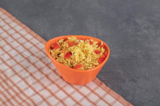 Рис с ломтиками помидора в апельсиновой миске. фото высокого качества
