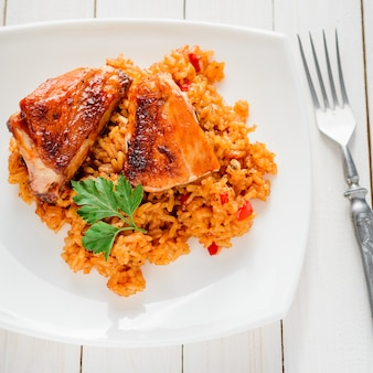 Rice with vegetables and baked chicken in a plate on a white table