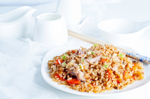 Rice with vegetables and chicken on a white background