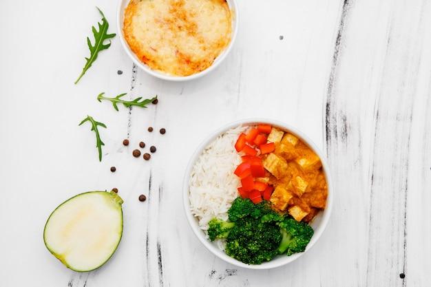 Рис с овощами в тарелке на белом фоне. вид сверху. свободное место для вашего текста.