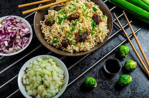 Rice with vegetables and meat on black table