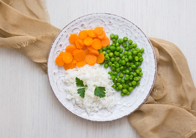 Rice with vegetables and parsley on plate with cloth