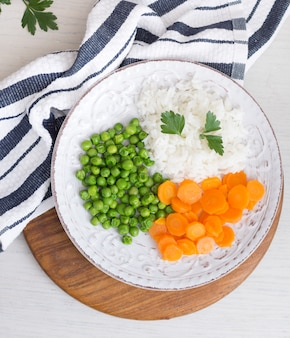 Rice with vegetables and parsley on wooden board near napkin