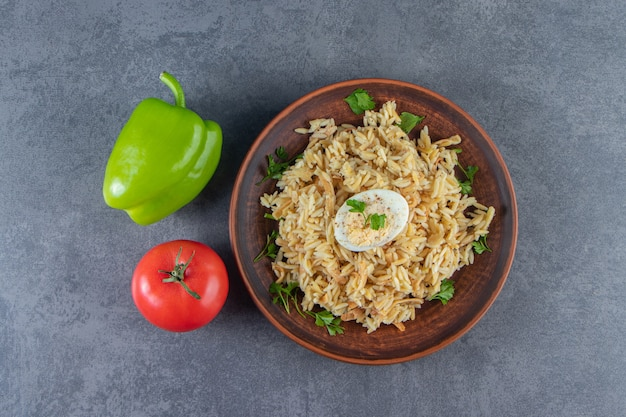 Рис с вермишелью на тарелке рядом с овощами на синей поверхности