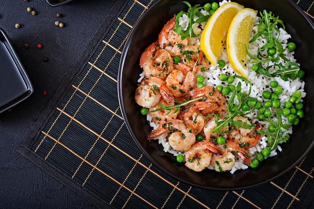 젊은 녹색 완두콩, 새우, 검은 그릇에 arugula와 쌀. 건강에 좋은 음식. 부처님 그릇. 평면도. 평평하다