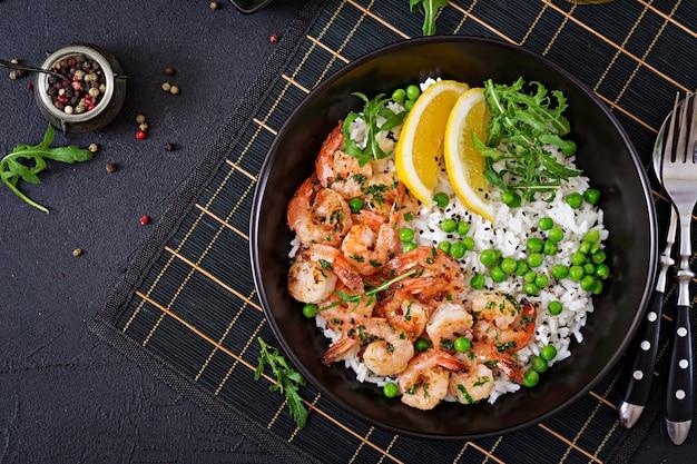 Рис с молодым зеленым горошком, креветками и рукколой в черный шар. здоровая пища. чаша будды.
