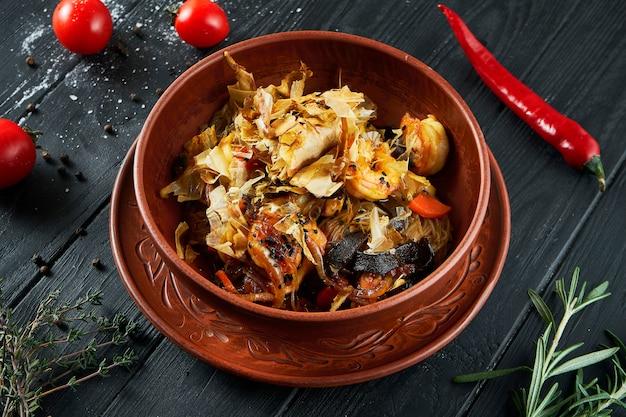Рисовая вок-лапша с морепродуктами (кальмары, креветки), соевым соусом и овощами в керамической миске на черном фоне.
