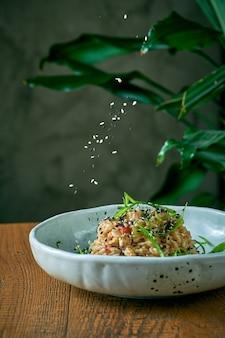 Рисовый вок с овощами и курицей в тарелке на деревянном фоне. азиатская кухня. в блюдо насыпают семена кунжута