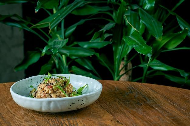 Рисовый вок с овощами и курицей в тарелке на деревянном фоне. азиатская кухня