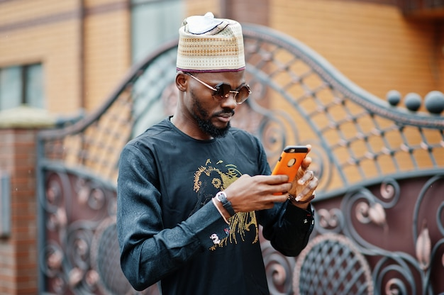 Rich african man in stylish traditional clothes and hat posed outdoor background his mansion, texting on mobile phone.