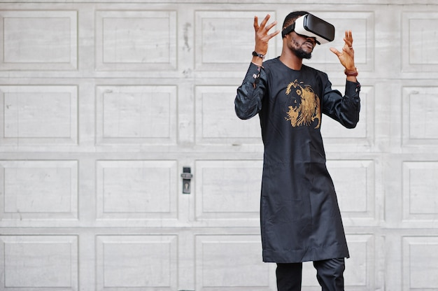 Rich african man in stylish traditional clothes in vr glasses. future of africa concept.