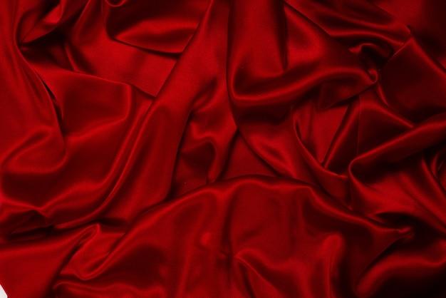Предпосылка текстуры богатой и роскошной красной шелковой ткани. вид сверху.