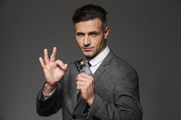 金色のスマートな男性30代のフォーマルなスーツとネクタイのプラスチック製のクレジットカードを示し、灰色の壁に分離されたokサインを身振りで示す