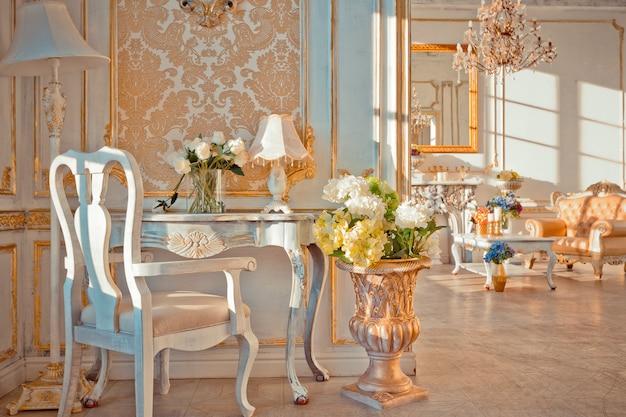 Богатый интерьер квартиры с золотым декором в стиле барокко на стенах и роскошной мебелью. комната залита лучами заходящего солнца