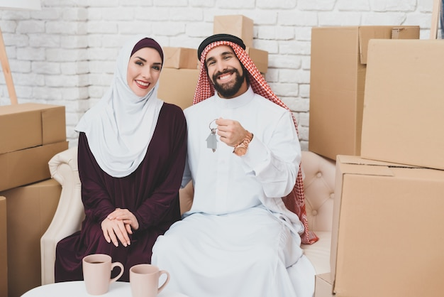 Rich arab home buyers near packed boxes housing.