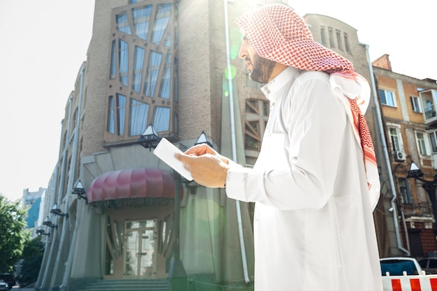부동산, 도시의 호텔을 사는 동안 부유한 아라비아 남자의 초상화. 민족, 문화, 포용, 다양성. 거래를 성공적으로 만드는 전통 의상을 입은 자신감 있는 사업가. 금융, 경제.