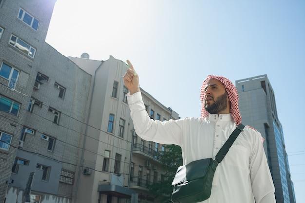 부동산을 사는 동안 부유한 아라비아 남자의 초상화, 도시에 사는 집. 민족, 문화, 다양성. 거래를 성공적으로 만드는 전통 의상을 입은 자신감 있는 사업가. 금융, 경제.
