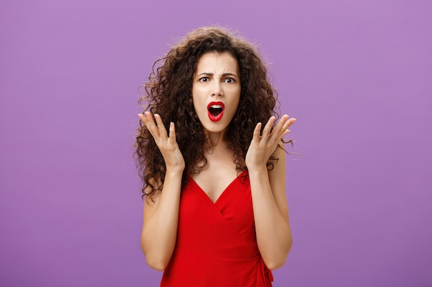 Rich arrogant and snobbish european woman with curly hairstyle in red evening dress arguing with made frowning looking confused and displeased shaking palms in disappointment posing over purple wall.