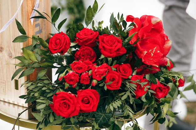 Rich bouquet made of red roses stands outside