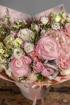 Богатый букет из розовых и красных цветов и сирени. эустома розы цветы цветут, зеленый лист в стеклянной вазе. свежий весенний букет. летний фон