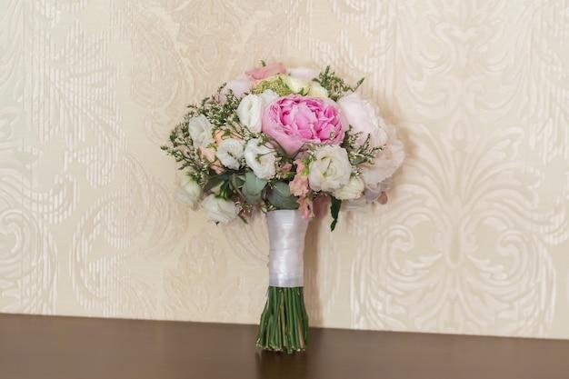 Богатый букет из розовых пионов и цветов лиловой эустомы, зеленый лист в окне. свежий весенний букет. летний фон