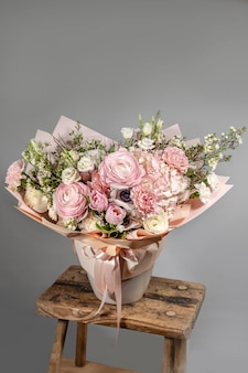 Rich bunch of pink and red flowers and lilac. eustoma roses flowers blossom, green leaf in glass vase. fresh spring bouquet. summer background
