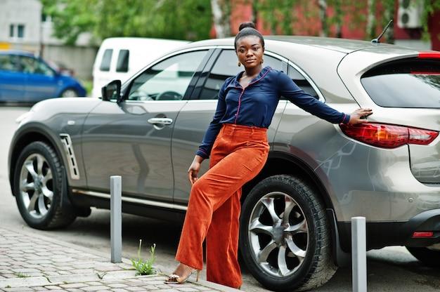 銀のsuv車に対して提起されるオレンジ色のパンツと青いシャツを着た豊かなビジネスアフリカ女性