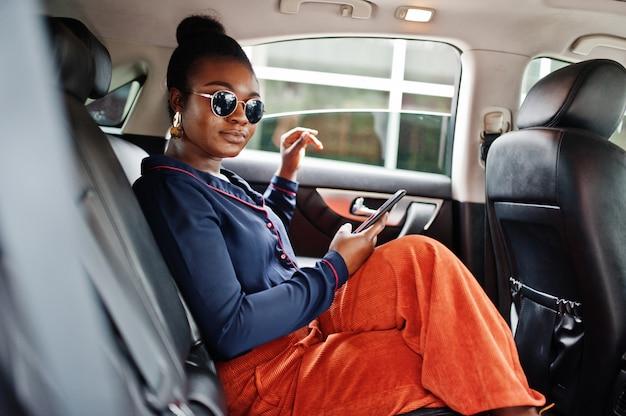 サングラスの豊かなビジネスアフリカ女性が黒い革張りのシートでsuv車に座っています。