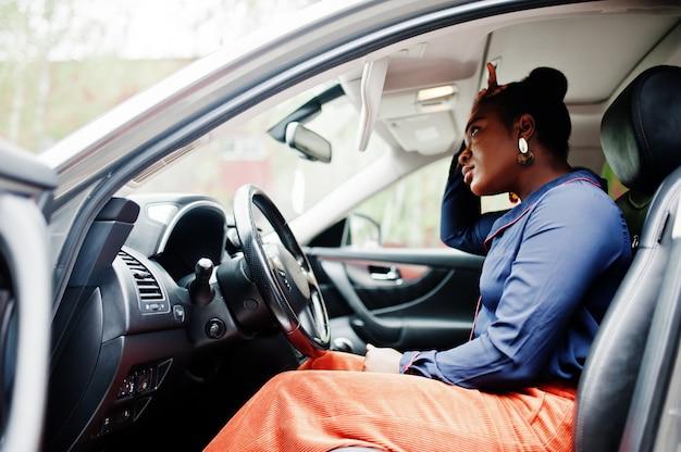 豊かなビジネスアフリカの女性が開いたドアと銀のsuv車で運転席に座る